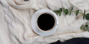 A cup of black coffee in a plate and green leaves
