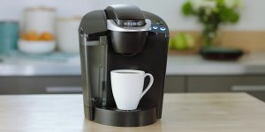 Electric coffee maker with a white cup
