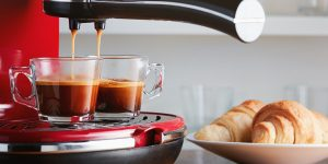 Two cups of brown coffee paired with breads